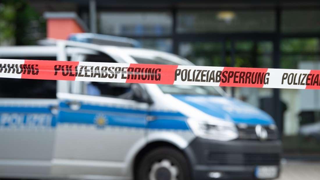 Ein Polizeiauto hinter einem Absperrband.