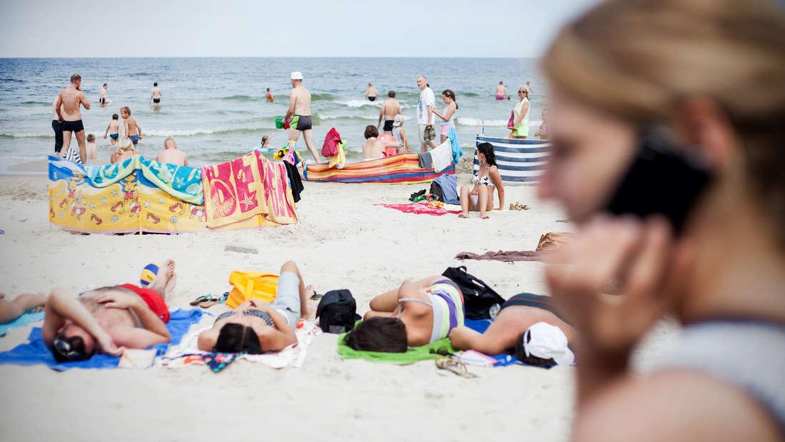Ein Strand mit mehreren Personen.