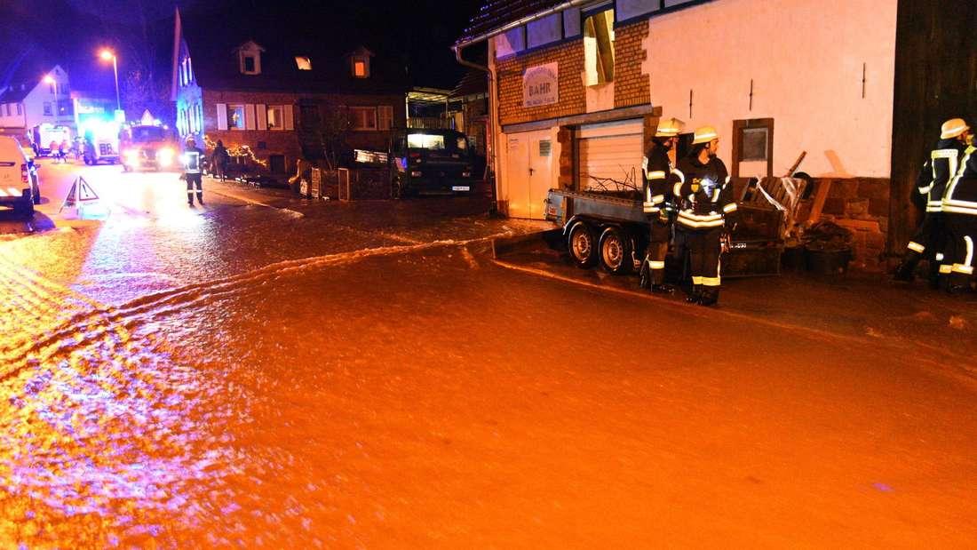 Einsatzkräfte der Feuerwehr stehen am 31.12.2017 in Waldhilsbach, einem Ortsteil von Neckargemünd, auf einer überfluteten Straße.