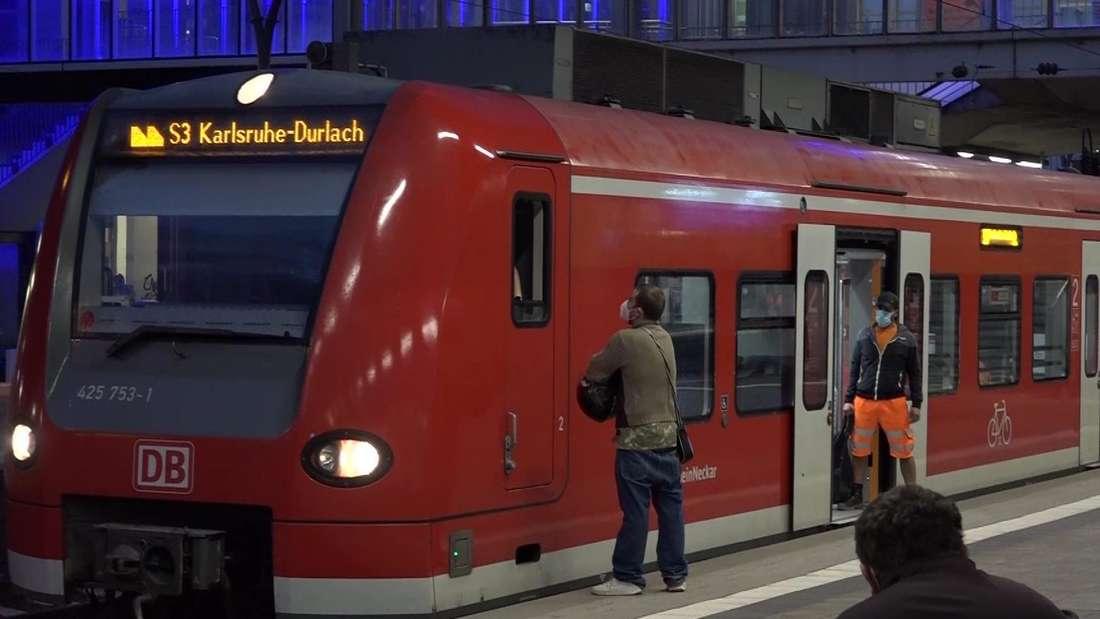 Ein Mann im Heidelberger Hauptbahnhof im Gespräch mit einem Lokführer.