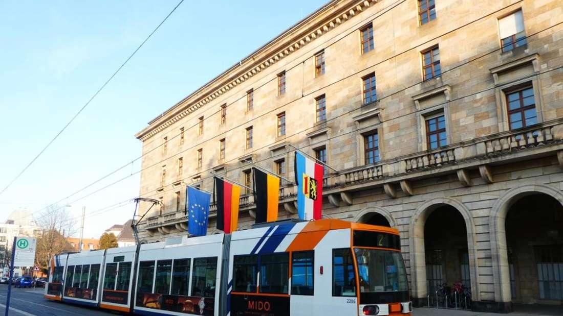 Das Rathaus von Mannheim mit vier Flaggen. Davor fährt eine Straßenbahn.