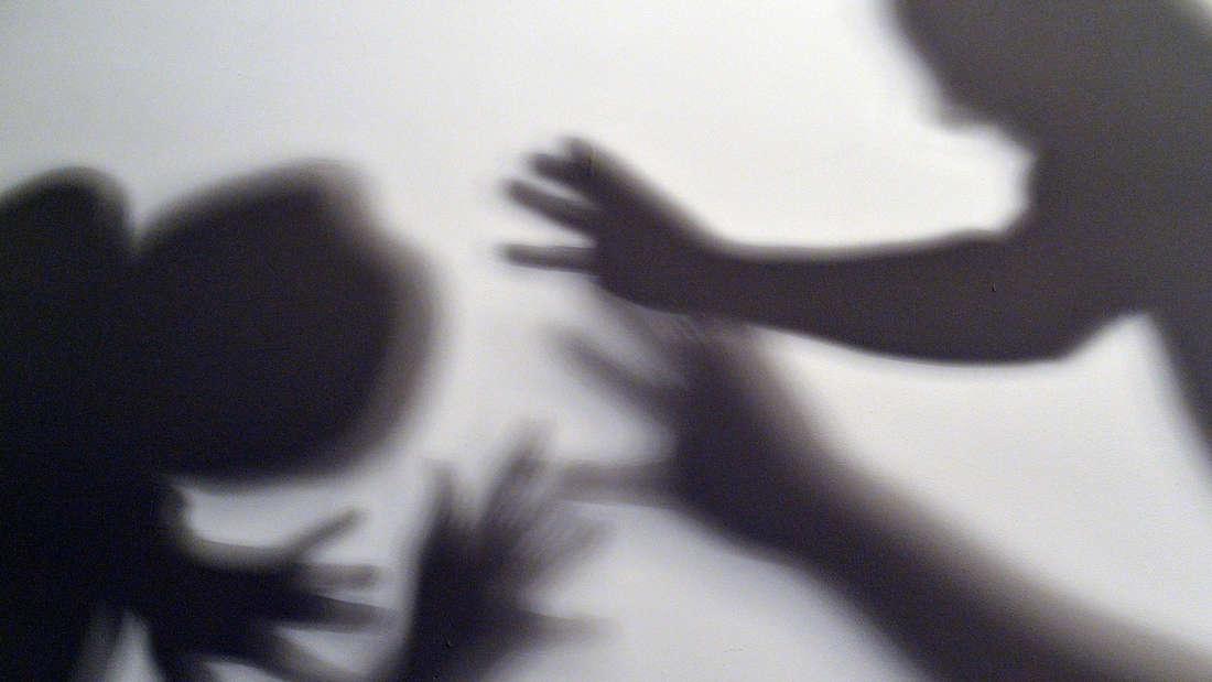Der Schatten eines Mannes bedroht den Schatten einer Frau.