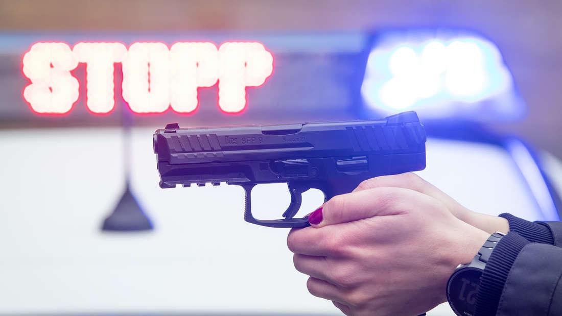 Ein Polizist hält eine Pistole.