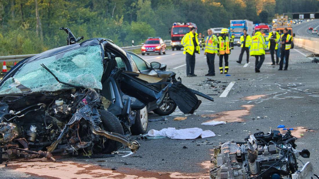 Helfer stehen auf der Autobahn 5 nach einem Unfall hinter einem Autowrack. Bei dem schweren Verkehrsunfall auf der A 5 bei Friedberg sind der Polizei zufolge mindestens vier Menschen getötet worden. Zudem seien mehrere Menschen verletzt worden, sagte ein Sprecher der Polizei.