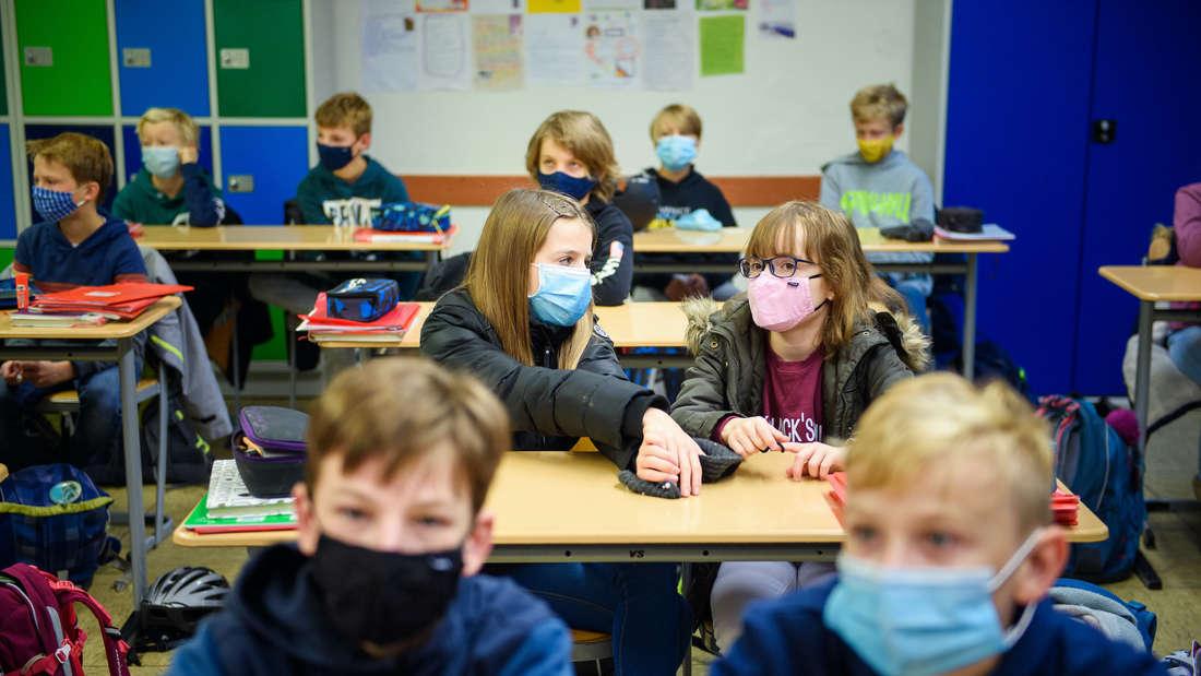 Kinder in einem Schulraum tragen eine Maske.