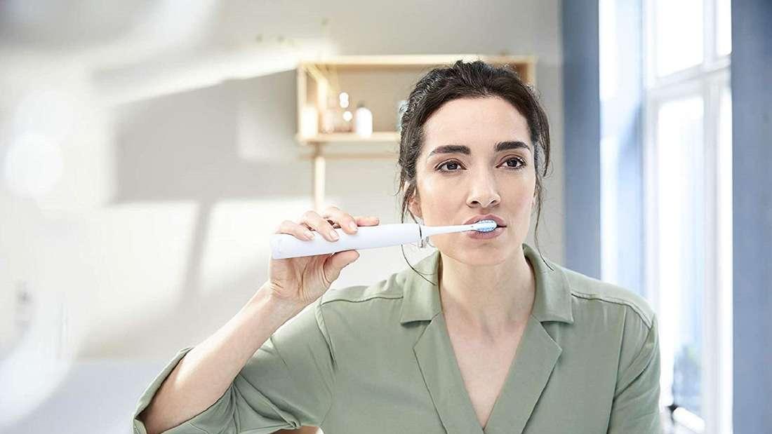 Eine Frau putzt ihre Zähne mit einer Philips Sonicare 7300 ExpertClean, schaut dabei in den Spiegel